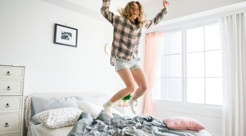 Vrouw springt op bed in slaapkamer